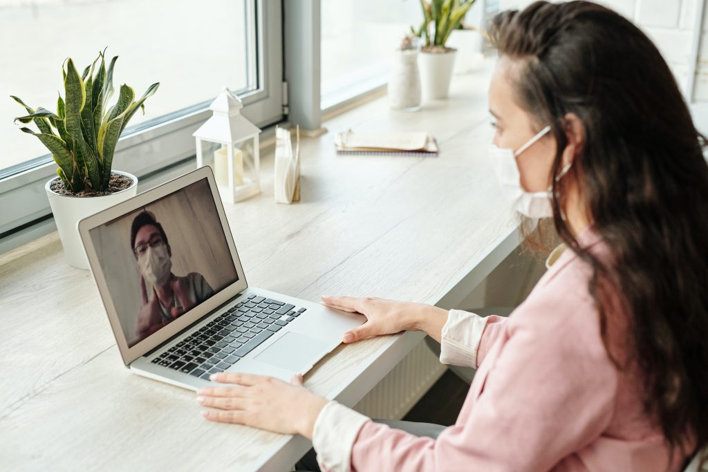 people having a video call with corona protection masks
