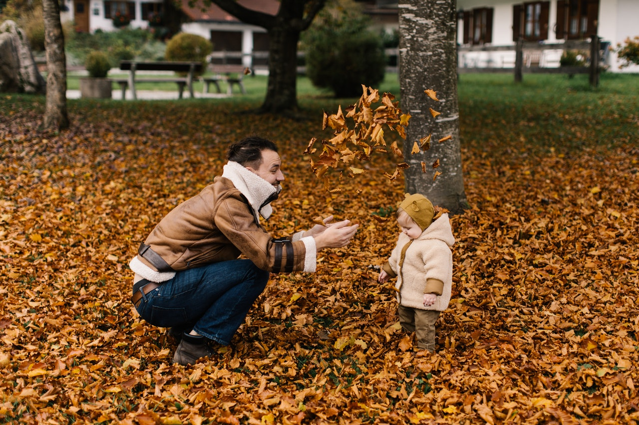 working remotely has this dad enjoying time with his child in the autumn leaves